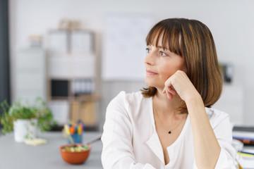 zufriedene geschäftsfrau am schreibtisch schaut zur seite