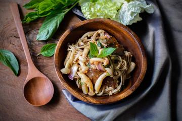 thai spicy mushroom salad in wooden bowl