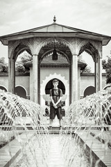 teenage boy standing at a fountain