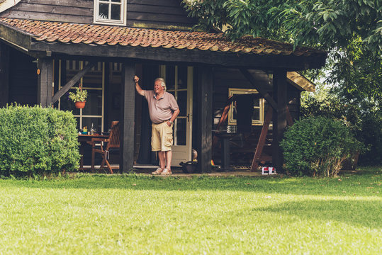 Retired man standing under porch of wooden house.