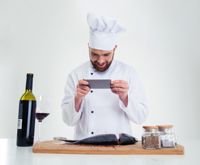 Chef cook making photo of fish on cutting board
