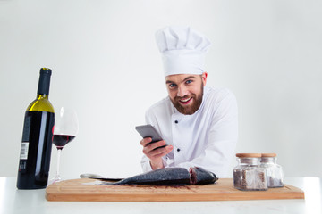 Smiling male chef cook using smarpthone