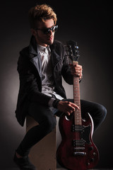 seated guitarist poses for the camera