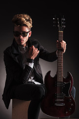 serious guitarist wearing sunglasses is sitting