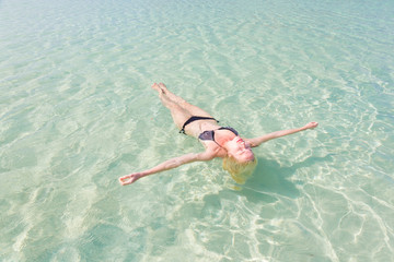 Caucasian lady floating in turquoise sea.