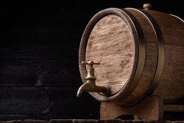 Vintage oak barrel on rack on old wooden table still life with copy space