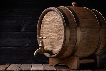 Vintage oak barrel on rack on old wooden table still life