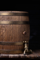 Old barrel with vintage tap on wooden table still life