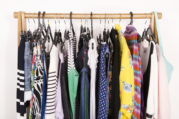 Close up on colorful clothes on hangers in a store.Clothes and accessories hanging on a rack nicely arranged.