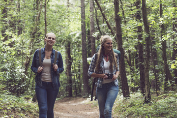 Happy twin sister walking on forest trail with backpack.