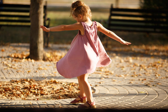 Full length portrait of a little girl dancing in the park a warm