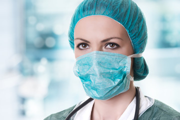 Closeup portrait of female doctor with stethoscope, bonnet and surgery mask on creamy blue background.