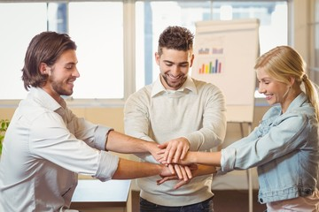 Smiling business people with hand stacked in meeting room
