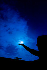 Woman holding full moon in hand against night sky