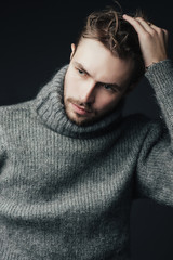 Portrait of a handsome young man with a beard in a warm sweater