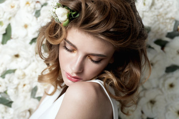 Portrait of a beautiful girl on a background of white flowers