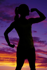 silhouette of woman fitness flex one arm look to side