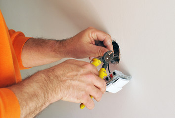 Un electricista instalando interruptores eléctricos nuevos, corte de cables con alicates