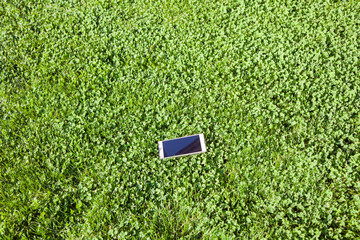 touch screen smart phone on the field of grass