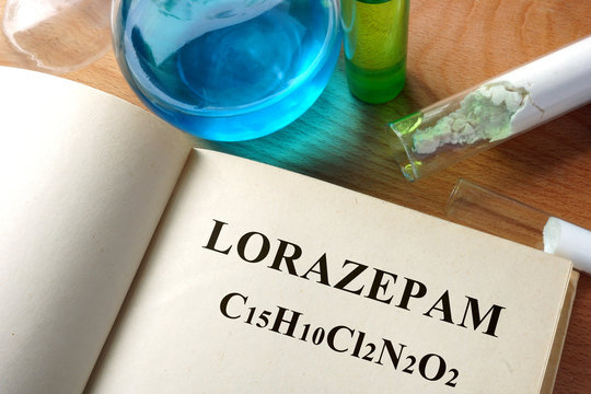 Book with Lorazepam  and test tubes on a table.