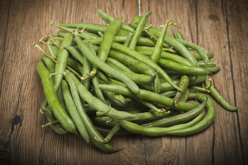 Group of green beans on the wood.