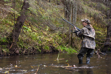 Canvas Prints Fishing Woman hunter shooting on the river