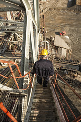 Coal mine worker photographed with a wide angle lens from a top of huge drill machine. Bird perspective. Back view.