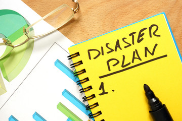 Notepad with disaster plan on a wooden table. Fotomurales