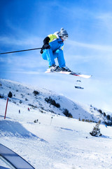 Jumping skier against blue sky