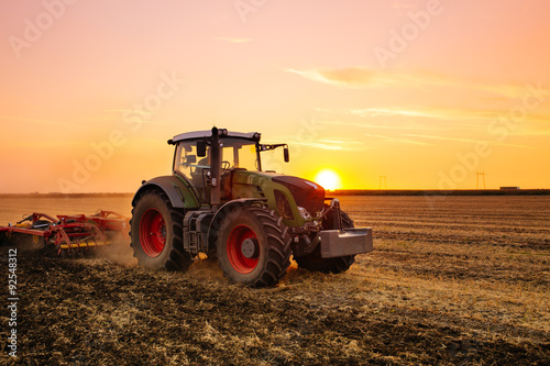 Wall mural Tractor on the barley field by sunset.
