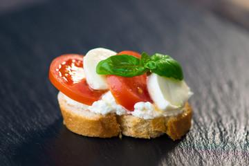Delicious slice of bread with buffalo mozzarella, tomatoes and fresh basil
