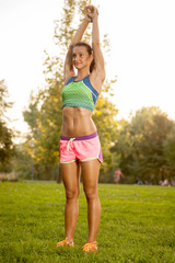 Fitness girl stretches in the park