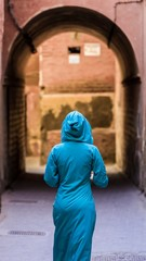 traditionally clothed arabic woman walking in the medina of marr