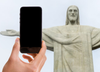 Hand holding mobile with black screen with Christ the Redeemer on background