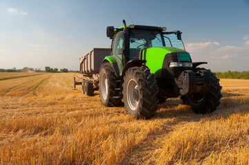 Modern green tractor on agricultural field during harvest on sunny summer day