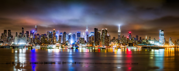 Fotomurales - New York City Panorama on a cloudy night as viewed from New Jersey across the Hudson River