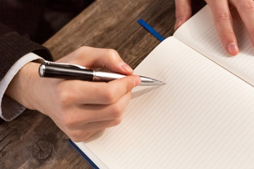 Man writing notes in personal notebook with elegant pen.