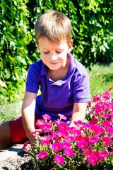 Cute boy smelling petunia flower
