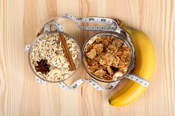 cereals,Bana, star anise, cinnamon, and oatmeal in a bowl and a measuring tape on wooden background