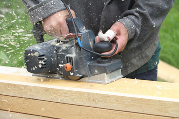 The man with the injured finger processes a board a electric planer outdoors