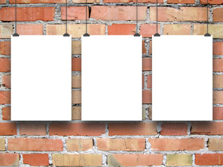Three paper sheets with clips on brick wall background