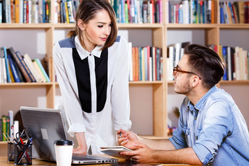 Young business woman and man are talking in office