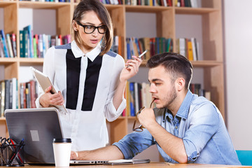 Young attractive woman and man are discussing about work