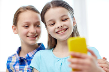 happy girls with smartphone taking selfie at home