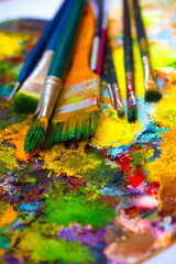 Paint brushes, painting palette with colors on white background