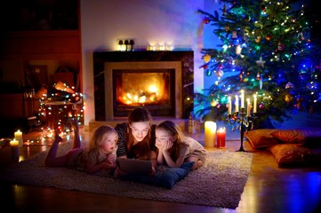 Mother and daughters using a tablet by a fireplace on Christmas