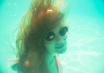 Young girl in sunglasses swimming underwater