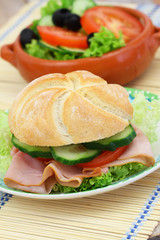 Lunch consisting of ham roll with lettuce, tomato and cucumber and green side salad