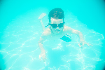 A little boy swimming underwater in the pool