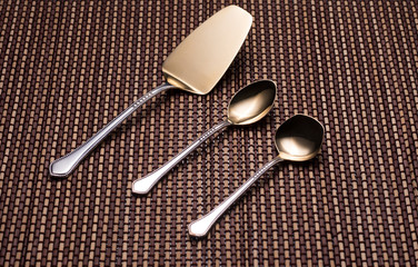 Silver kitchen utensils with golden spraying at the end.